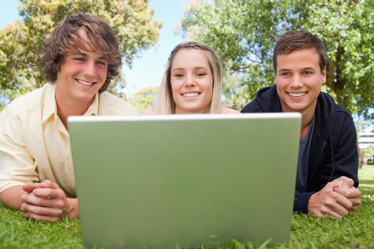 Three smiling students in a park lying while using a laptop