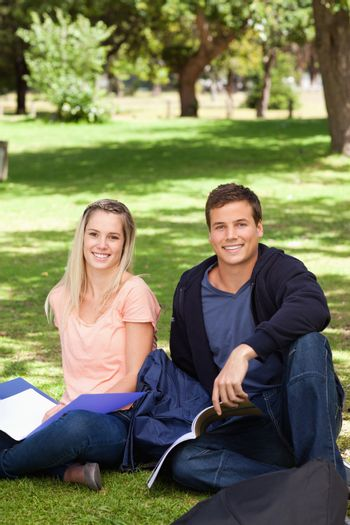 Portrait of two students in a park studying