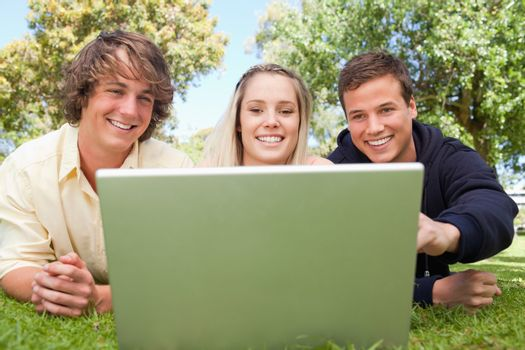 Portrait of three happy students in a park lying while using a laptop