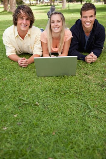 Three smiling students with a laptop in a park