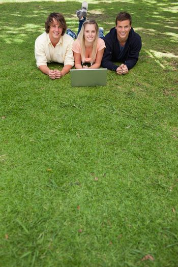 Three smiling students lying in a park with a laptop