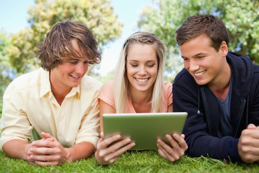 Three students using a tactile tablet while lying in a park
