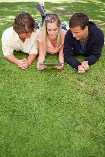 Three young people using a tactile tablet while lying in a park
