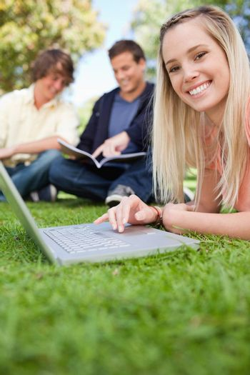 Close-up of a girl using a laptop while lying in a park with friends in background