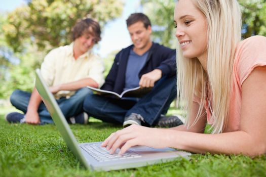 Girl using a laptop while lying in a park with friends in background