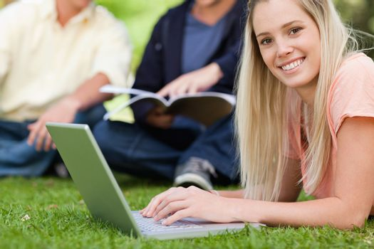 Portrait of a smiling girl using a laptop while lying in a park with friends in background