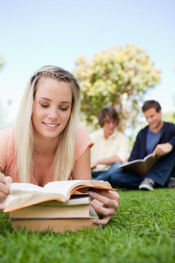 Close-up of a girl lying while reading books in a park with friends in background