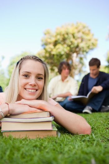 Close-up of a girl lying head on her books in a park with friends in background