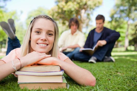 Porrtait of a girl lying head on her books in a park with friends in background