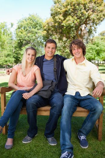 Three smiling students on a bench in a park together