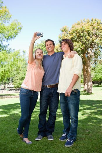 Three smiling students taking a pictures of themselves in a park