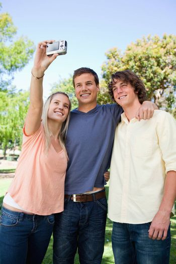 Three smiling friends taking a pictures of themselves in a park