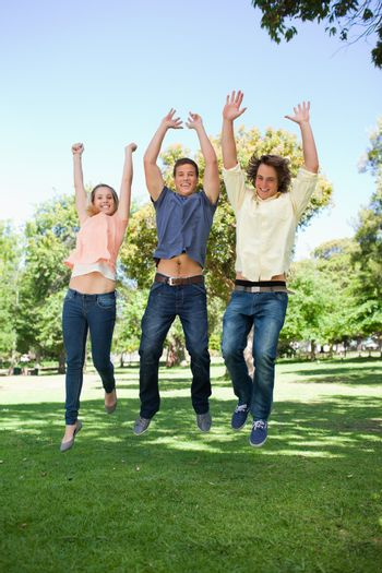 Three students jumping in a park