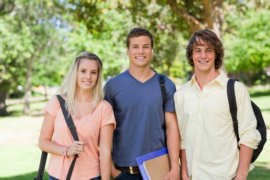 Portrait of Three students side by side in a park