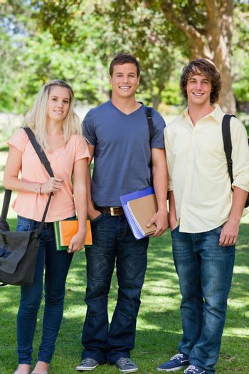Three students posing side by side in a park