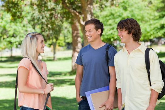 Girl speaks to two students in a park