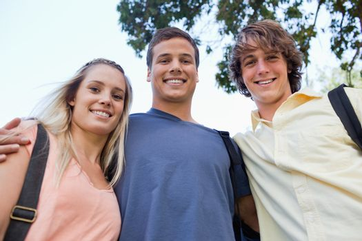 Low angle-shot of three students shoulder to shoulder in a park
