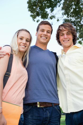 Low angle-shot of three friends shoulder to shoulder in a park