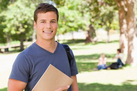 Portrait of a student smiling while holding a textbook in a park with friends in background