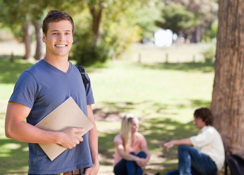 Portrait of a smiling student holding a textbook in a park with friends in background