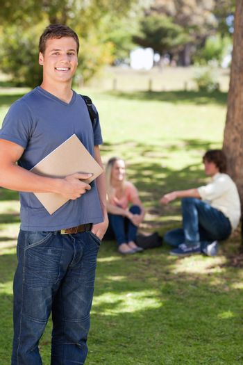 Student smiling while holding a textbook in a park with friends in background
