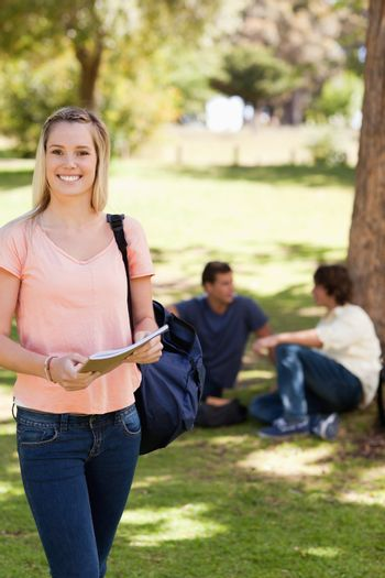 Portrait of a smiling female holding a textbook in a park with friends in background