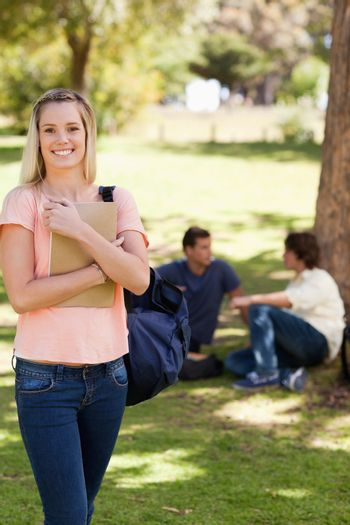 Smiling female holding a textbook in a park with friends in background