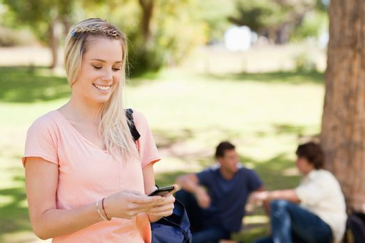 Close-up of a smiling girl using a smartphone in a park with friends in background