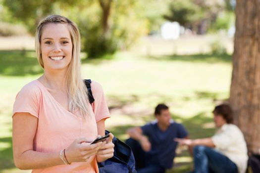 Portrait of a smiling girl using a smartphone in a park with friends in background