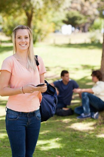 Portrait of a happy girl using a smartphone in a park with friends in background