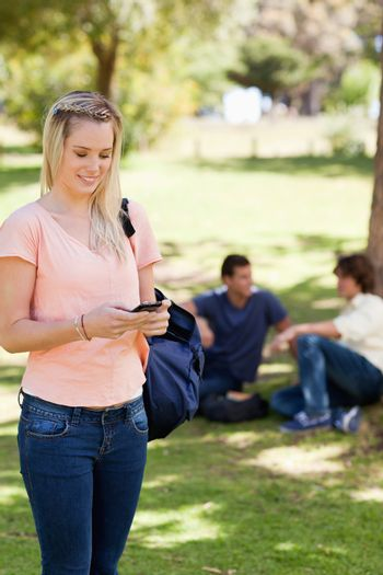Standing girl using a smartphone in a park with friends in background