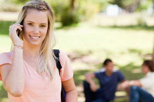 Close-up of a girl on the phone in a park with friends in background
