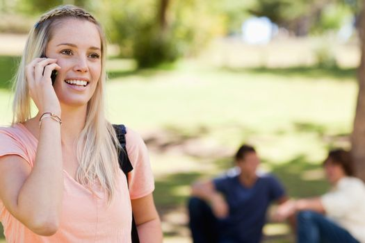 Close-up of a student on the phone in a park with friends in background