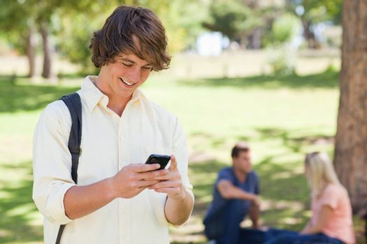 Close-up of a young man using a smartphone in a park with friends in background