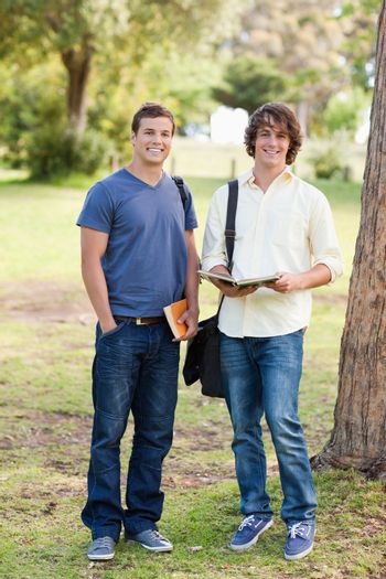 Portrait of two smiling male students posing in a park