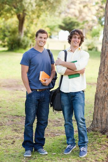 Portrait of two happy standing male students in a park