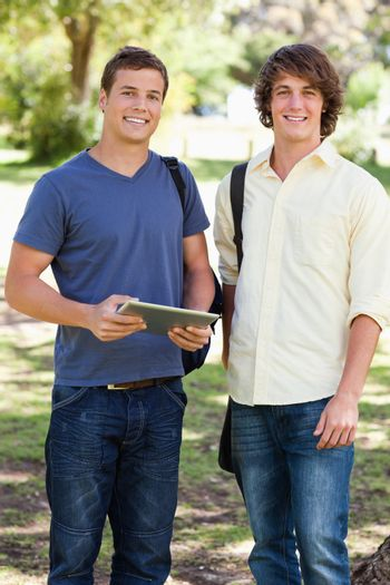 Portrait of two smiling male students with a touch pad in a park