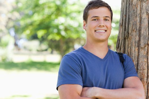 Portrait of a young man leaning against a tree in a park