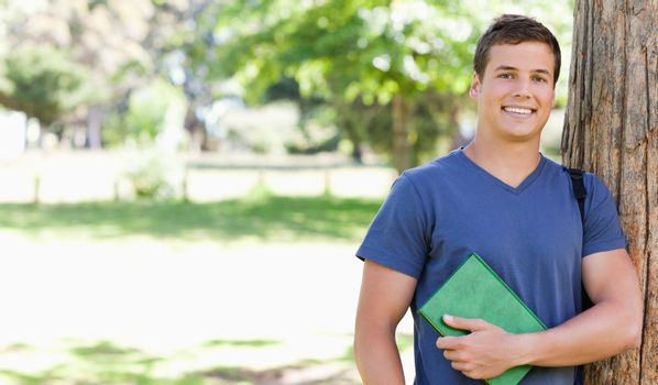 Portrait of a smiling muscled student holding a textbook in a park