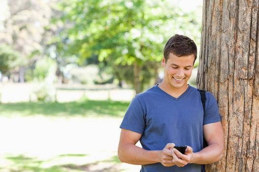 Muscled student using a smartphone in a park