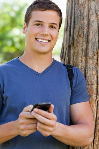 Portrait of a muscled student man using a smartphone in a park
