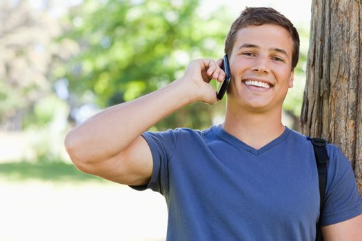 Close-up of a muscled young man on the phone in a park