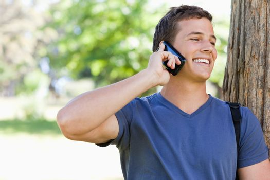 Close-up of a muscled student on the phone in a park