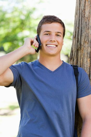 Portrait of a muscled young man on the phone in a park