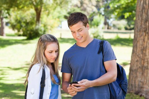 Close-up of a student showing his smartphone to a girl in a park