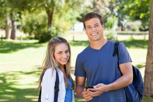 Portrait of a student showing his smartphone screen to a girl in a park