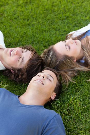 Three students lying together in the grass