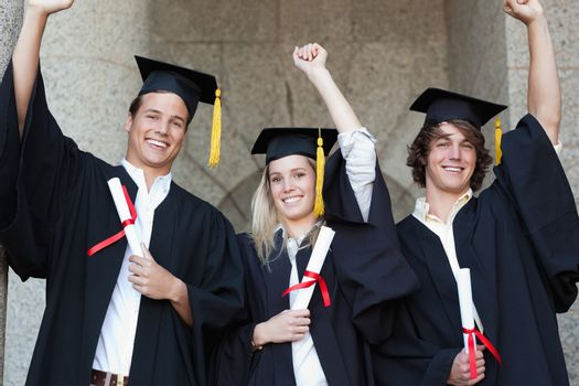 Graduates holding their diploma while raising arm with university in backgroung