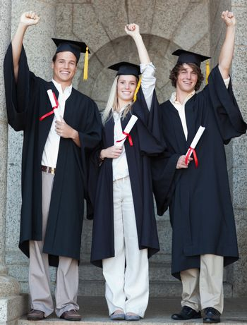 Smiling graduates raising arm with university in backgroung
