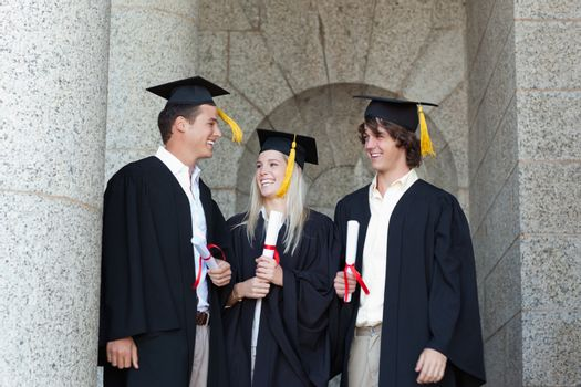 Happy graduates speaking together with university in backgroung